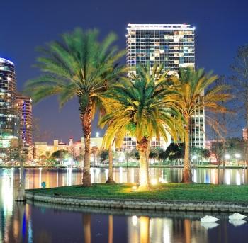orlando centro de ciudad panorámica sobre el lago eola en la noche con los rascacielos urbanos, los árboles del trópico de palma y el cielo claro.